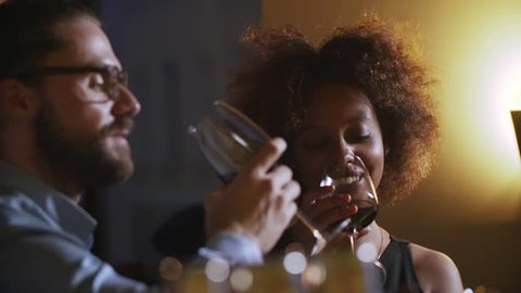 Young Couple Toasting Wine Glass In Luxury bar. Dating. Hipster and black woman on romantic dinner drinking at bar