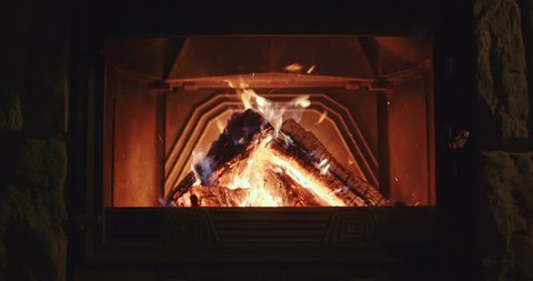 Close Up of Wood Burning in a Fireplace. 4K DCi SLOW MOTION 120 fps. Warm cozy fire in a hearth or fire pit. Calm Nature loopable Background. Autumn and Winter holidays. Chalet or Cabin comfort.