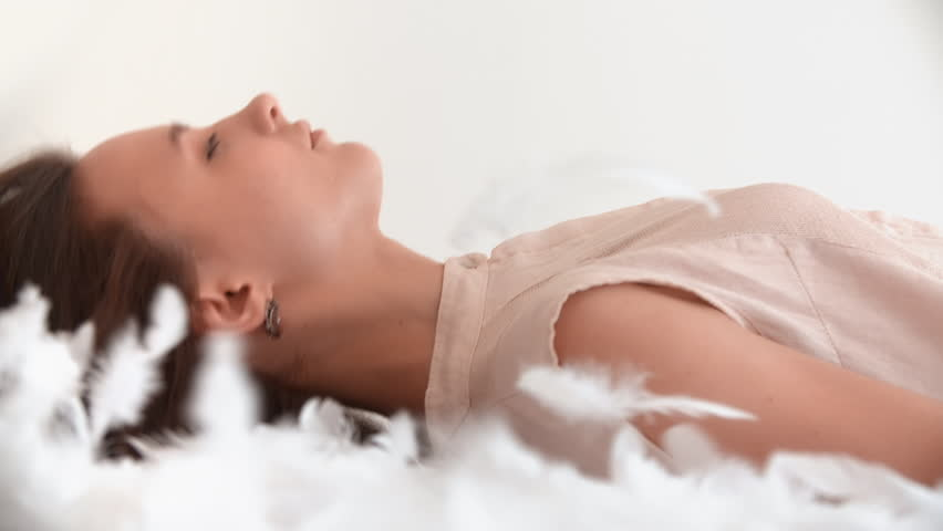 Young woman falling down on the bed with white flying feathers