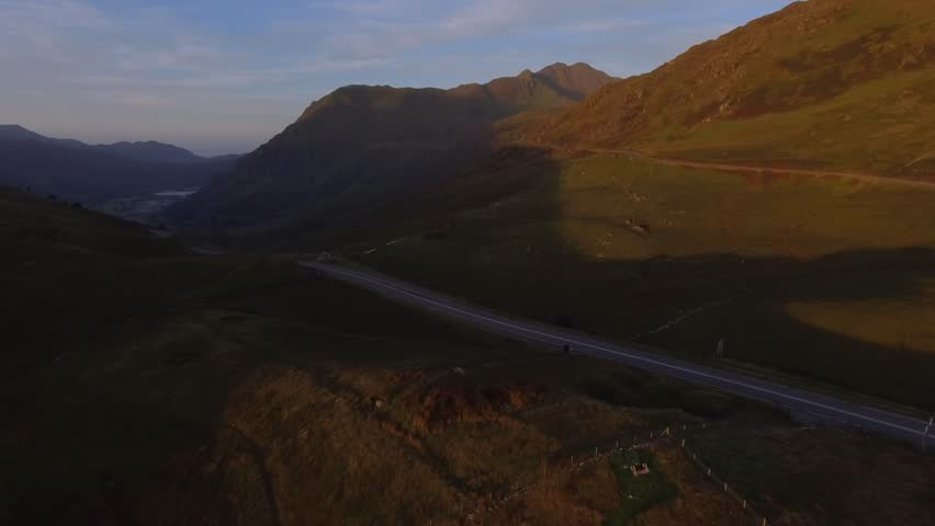 Drone aerial footage over park in soft light at sunrise. Traveling down towards a road in the valley where some sheep can be seen moving across the hill side. | Shutterstock HD Video #19402204