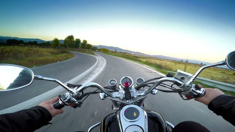 Driving motorbike on asphalt road. POV