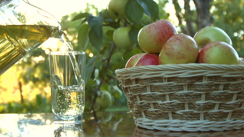 green and red apples in basket. from the pitcher is poured into a glass of juice on background growing apples green and red in basket