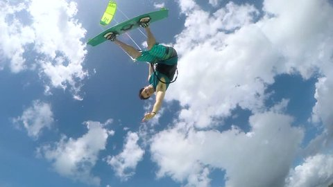 SLOW MOTION: Happy smiling kite surfer jumping and showing shaka sign in turquoise ocean on sunny day. Extreme cheerful kiteboarder man kiting and jumping over camera in blue lagoon on summer vacation