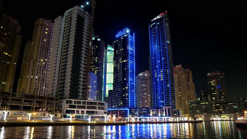 8K Dubai Marina night time lapse, UAE. Dubai Marina - the largest man-made marina in the world, is a canal city, carved along a 3 km stretch of Persian Gulf shoreline. Dubai 8K 7680x4320 Timelapse