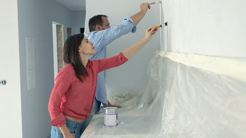 Happy, young couple talking while painting wall in kitchen at their new home