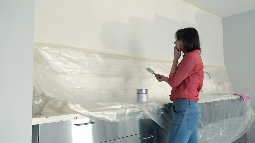 Unhappy woman painting wall in kitchen at her new home  | Shutterstock HD Video #19457764