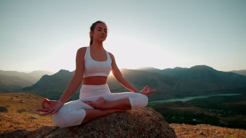4K beautiful girl in white clothes doing yoga in the beautiful mountains,sunrise, slow motion