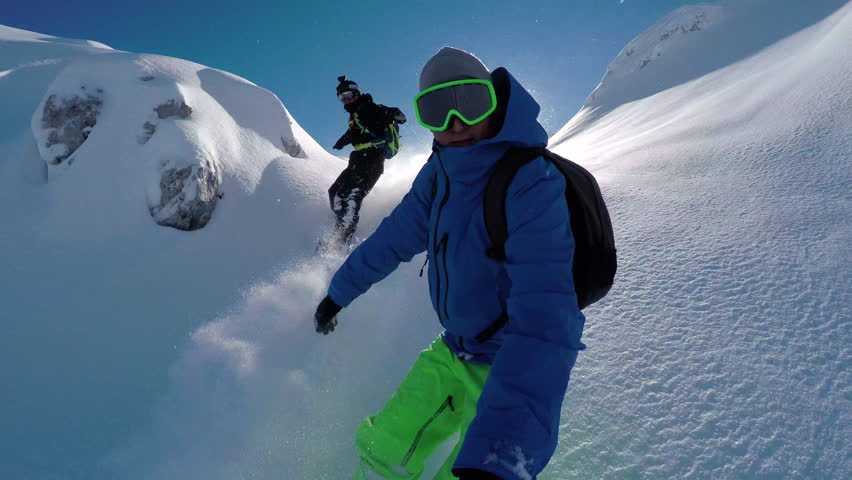 SELFIE: Cheerful snowboarders having fun snowboarding backcountry on sunny winter day in snowy mountains. Extreme freeride snowboarders riding fresh powder snow and doing powder turns off piste