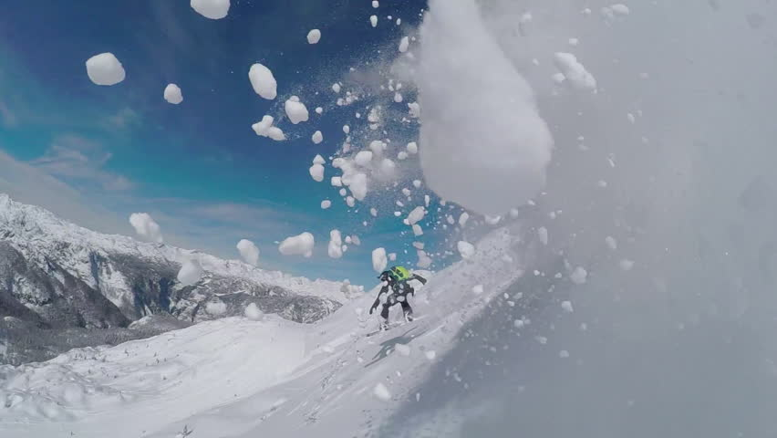 SLOW MOTION: Happy snowboarder having fun snowboarding backcountry on a sunny winter day in snowy mountains. Extreme freeride snowboarder riding fresh powder snow off piste in mountain ski resort