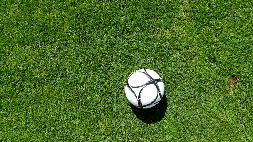 Footballer leading the ball on a football field, top view
