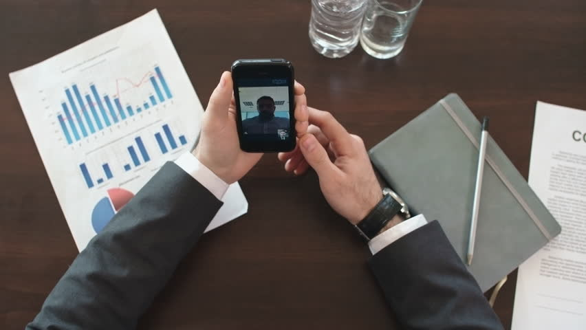 Directly above view of office worker sitting at desk and talking with business partner via video calling on his smart phone | Shutterstock HD Video #19484314