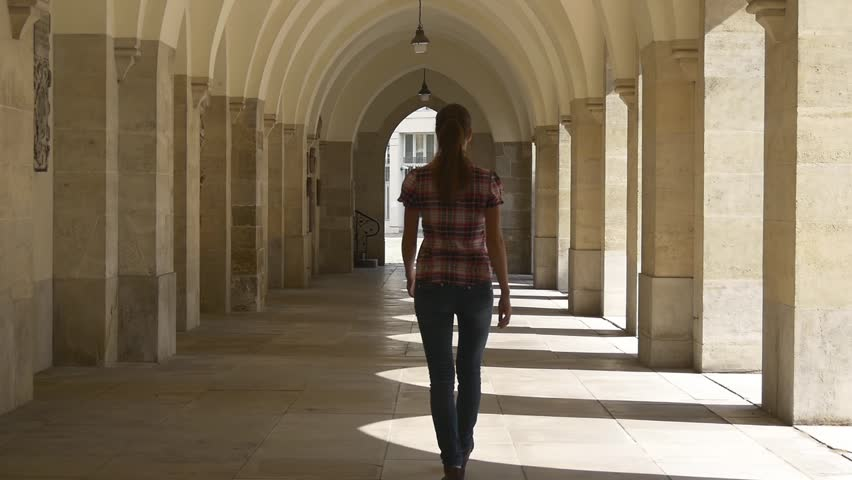 Young woman walking through the arches of the historical buildings away from the camera | Shutterstock HD Video #19498774