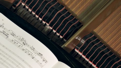 MINSK, BELARUS - NOV 21, 2015: Piano mechanism operates during a concert. Strings, hammers and dampers. Music sheets of VII century classics. (av24933c)
