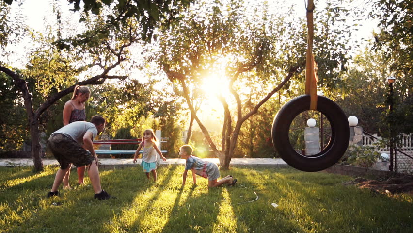 Parent playing with small two happy children at home on backyard with swing and trees during sunset. Slowmotion