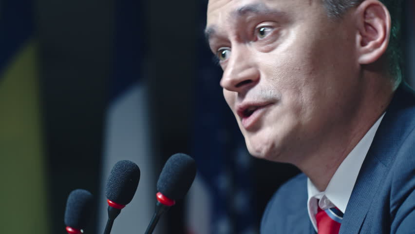 Profile of mature male politician speaking passionately and aggressively from tribune at political debates | Shutterstock HD Video #19522651