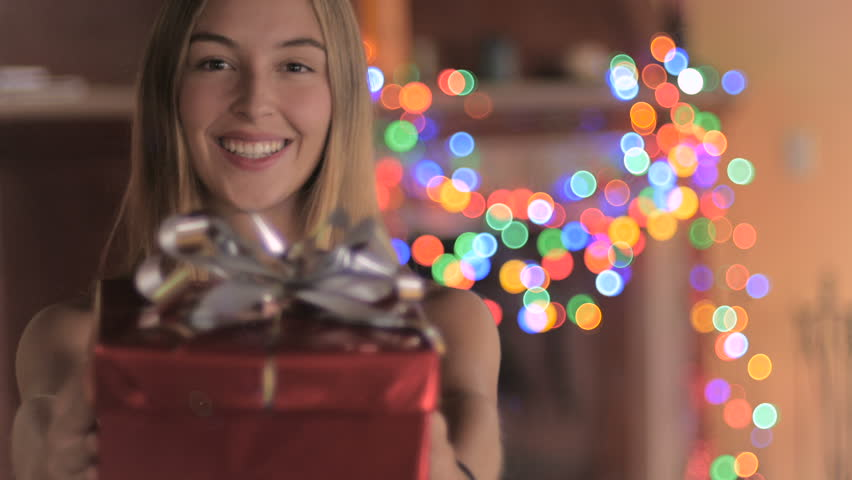 An attractive young woman wearing a Santa hat gives a red wrapped wrapped gift with a silver bow and laughs with colored lights flashing in the background #19530835