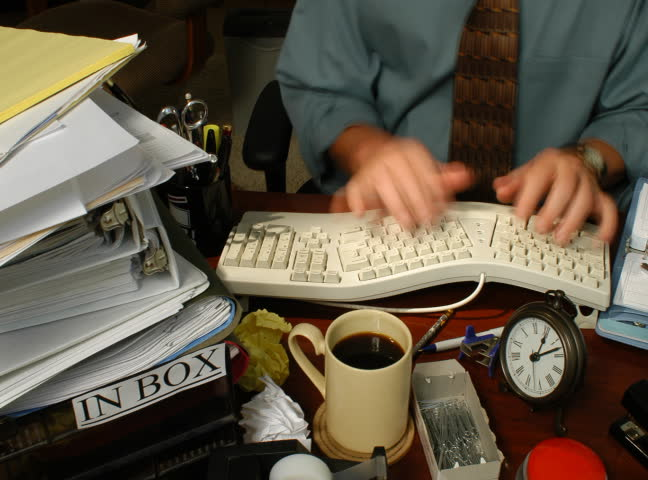 Timelapse of Office worker who hurries to finish piles of work in his inbox. Could be intercut with clip @190942