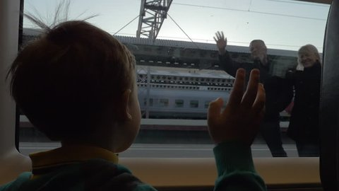 Slow motion shot of a boy in departing train and grandparents outside waving hands to each other to say goodbye