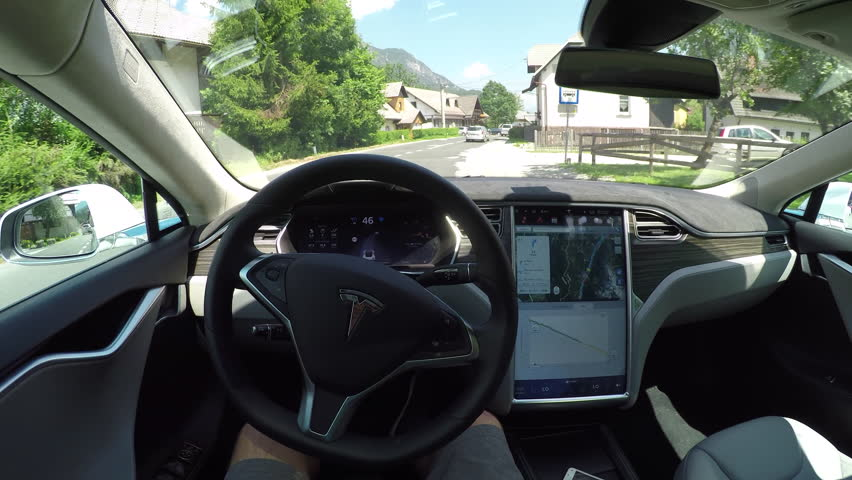 KRANJSKA GORA, SLOVENIA - JULY 17 2016: Unrecognizable person self driving autonomous electric car, navigating and steering without driver on countryside road. Vehicles coming on the opposite side