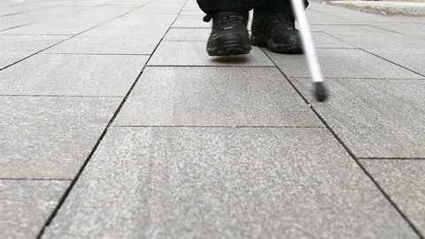 Blind man walking with his white cane / Slow motion