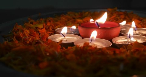 Extreme close up of someone blowing off  Diyas or indian earthen lamp in a silver plate with marigold petals, lit up for Diwali 'Festival of light',surrounded by lit tea-light candles