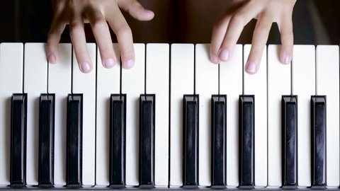 the hand on piano key in close-up shot. child learning to play the piano