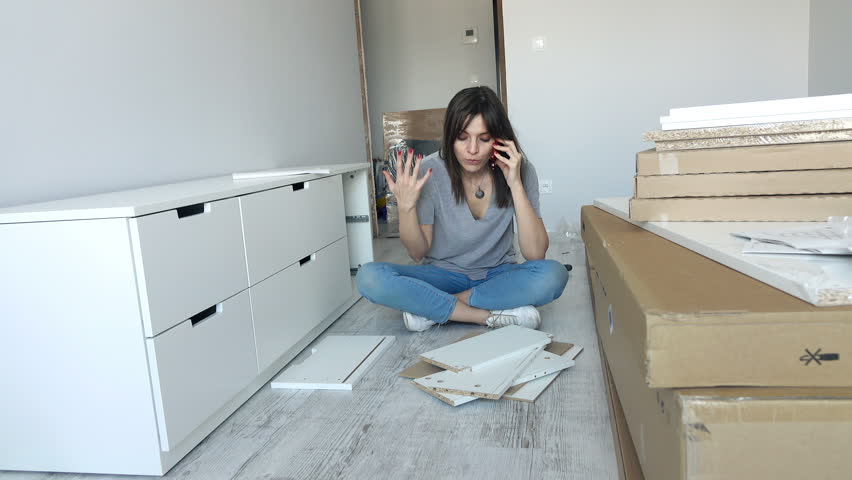 Unhappy woman talking on cellphone and trying to match pieces of furniture on floor at home   | Shutterstock HD Video #19616554