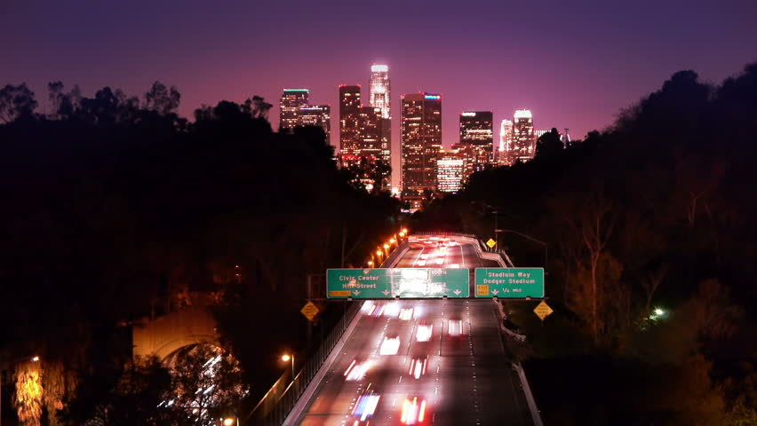 Downtown Los Angeles skyline and freeway city traffic at night. Timelapse.