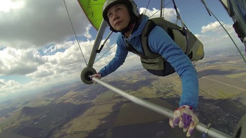 Woman flies on a hang glider with a bird. Eagle tried to attack hang glider circling above and around it, releasing claws and making offensive maneuvers