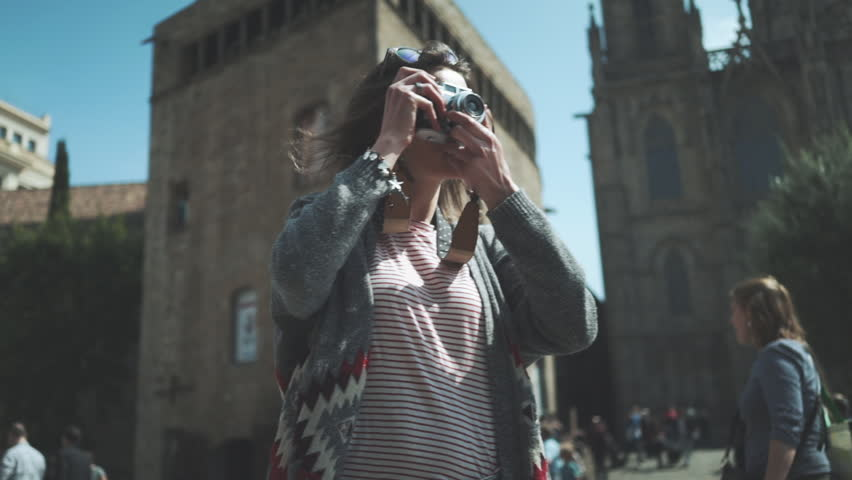 Portrait shot of young hipster traveler girl walking in the city and take picture via vintage camera outside, attractive woman traveling at Europe looking landmarks in Barcelona, slow motion | Shutterstock HD Video #19637392