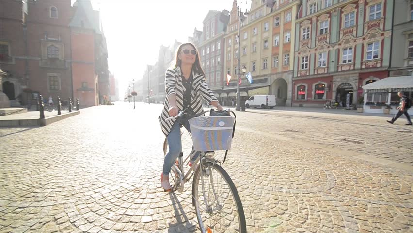 Beautiful young woman smiling while riding her bicycle on a sunny summer day through town in Slow Motion