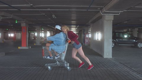 MED fashion funny young hipster teen girls having fun at the shopping mall parking, riding in shopping cart. 60 FPS 4K UHD