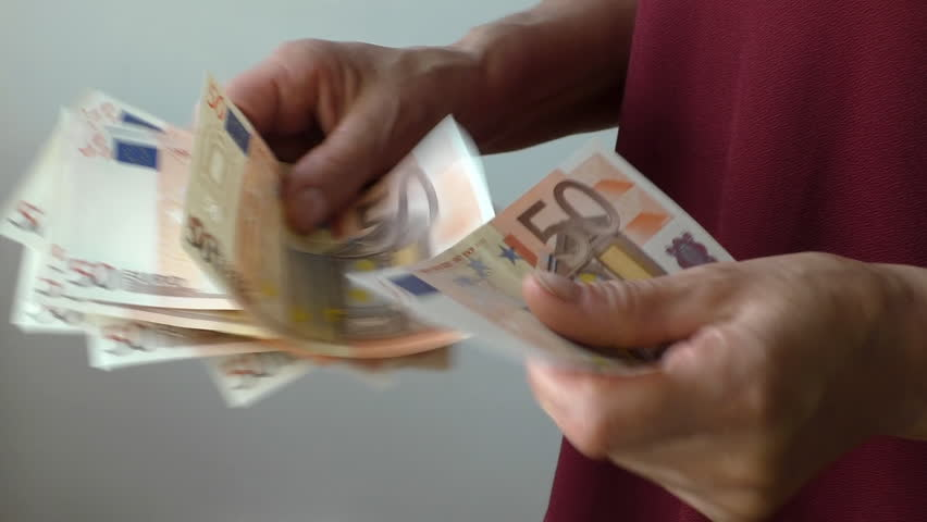 Close up of hands of a woman standing near grey gray wall and counting her money, 50 euro bills banknotes | Shutterstock HD Video #19690474