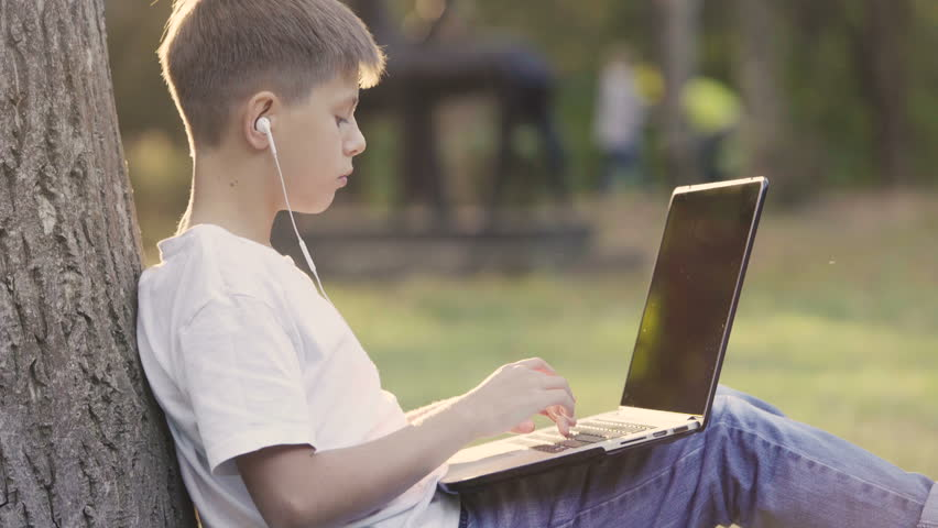 Concept of learning and lifestyle in teens life. Young teenage boy in park sitting under tree in garden and using a laptop. 4K video