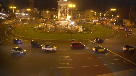 Plaza de Espana in Barcelona, top view at night, cars driving around fountain
