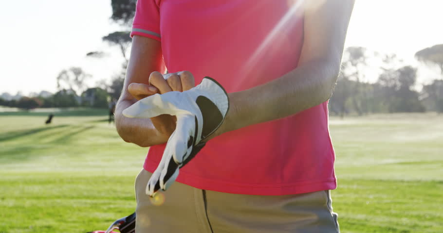 Female golfer wearing golf glove at golf course
