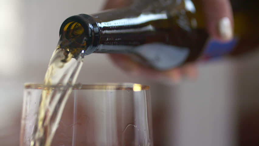 Beer is pouring into the glass in native slow motion scene, forming waves and splashes | Shutterstock HD Video #19751143