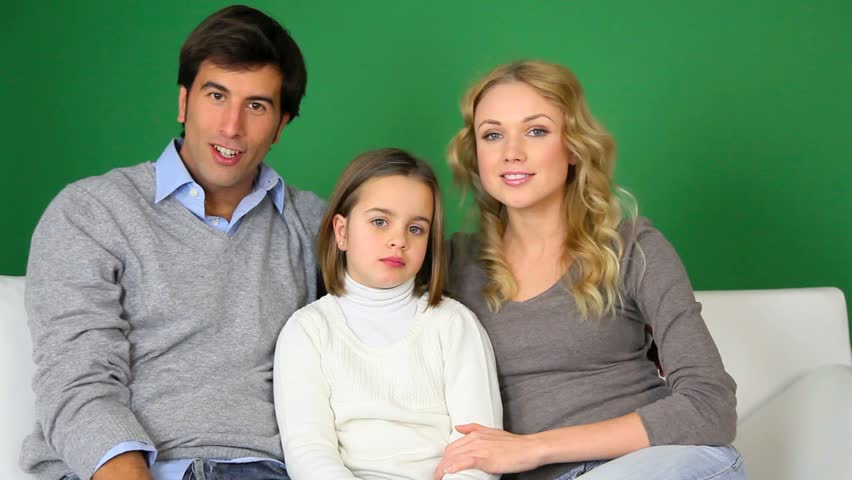 Cheerful family sitting in sofa and talking to camera