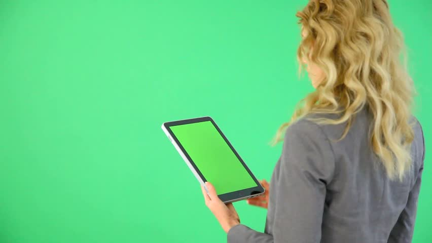 Backview of businesswoman on green background with digital tablet