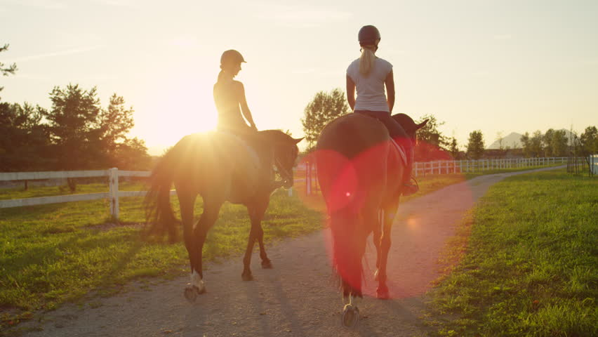 SLOW MOTION, CLOSE UP: Two young girls horseback riding amazing strong brown stallions walking into magical golden sunset on beautiful horse ranch farm. Girlfriends on relaxing morning ride at sunrise