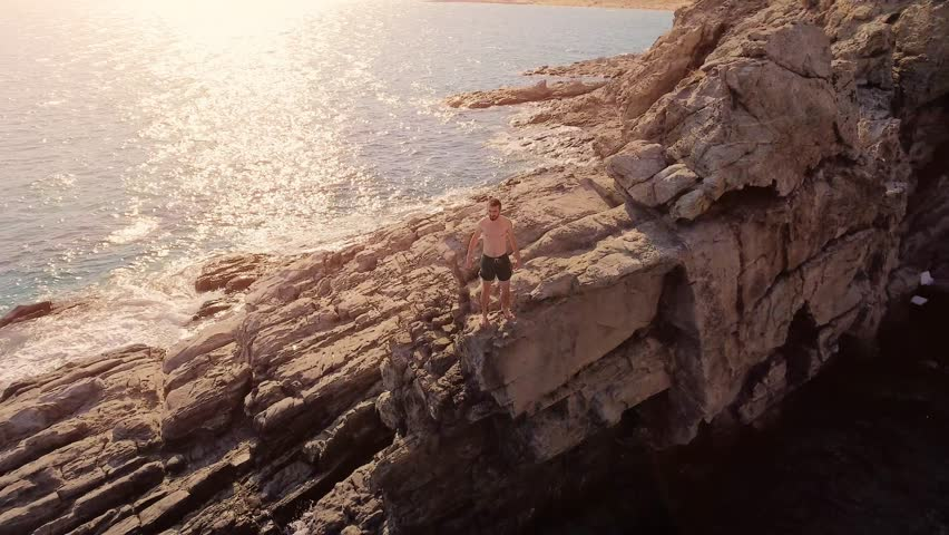 Athletic Young Man Standing On The Edge Of Cliff Before Jump At Sunset Extreme Sports Vacation Adrenaline Success Holiday Beautiful Island Location Beach Ocean Concept