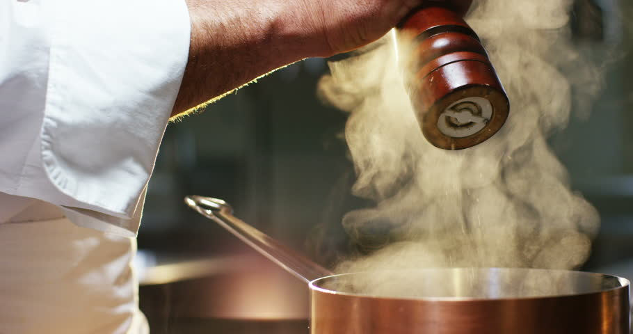 in an Italian professional kitchen a chef pours pepper in slow motion on a dish or in the water to boil the Italian pasta concept of healthy and light food. bio