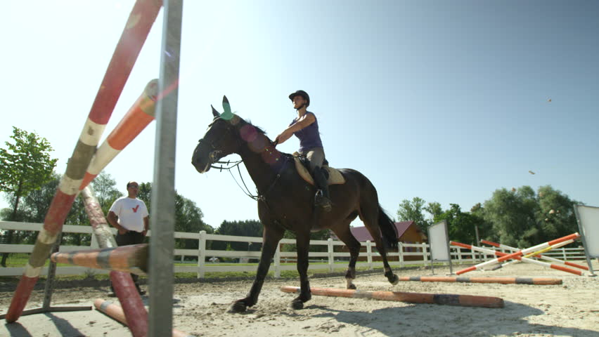 SLOW MOTION, CLOSE UP, LOW ANGLE: Horsegirl riding strong brown horse jumping the fence in sunny outdoors sandy parkour dressage arena. Competitive rider training jumping over obstacles in manege #19799374