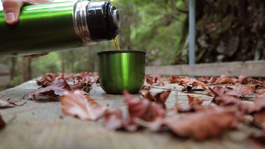 Man pours tea from a thermos into a mug on a wooden table among the autumn leaves. Wind blowing autumn leaves. Autumn mood background. Concept of the season, mood, hike, travel, time. | Shutterstock HD Video #19802344