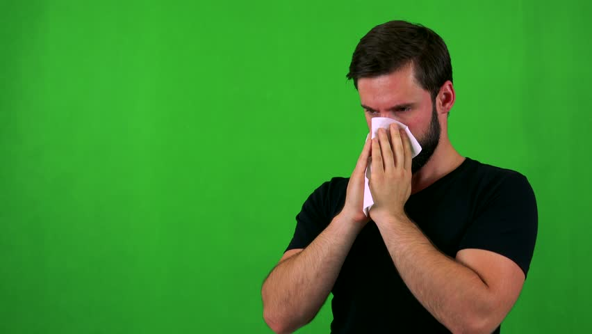 young handsome bearded man blow one's nose - green screen - studio