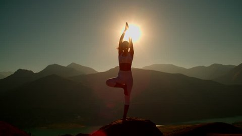 4K yoga in the mountains,the sunrise, a beautiful girl dressed in white ,pulls his hands to the sun