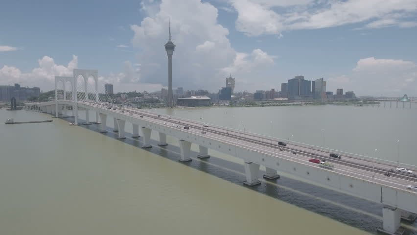 MACAU - JULY 2016: Aerial view of a long cable-stayed bridge connecting Macau peninsula (the iconic tower and casinos are visible) with Taipa island.