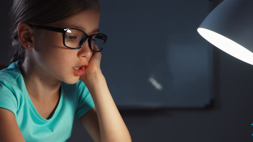 Close up portrait school girl 7-8 years old in glasses reading a book in the night in her desk and smiling at camera. Panning | Shutterstock HD Video #19842274