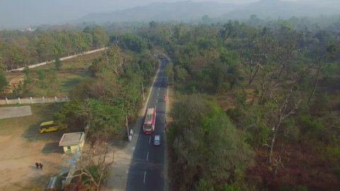 Aerial shot following a bus driving through rural countryside in India. Two lane road with pedestrians, motorcycles, cars. Lush green forest/woods and light smog/haze in distance.