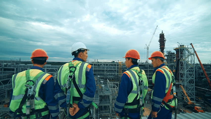 Workers at refinery as team discussing, industrial scene in background.